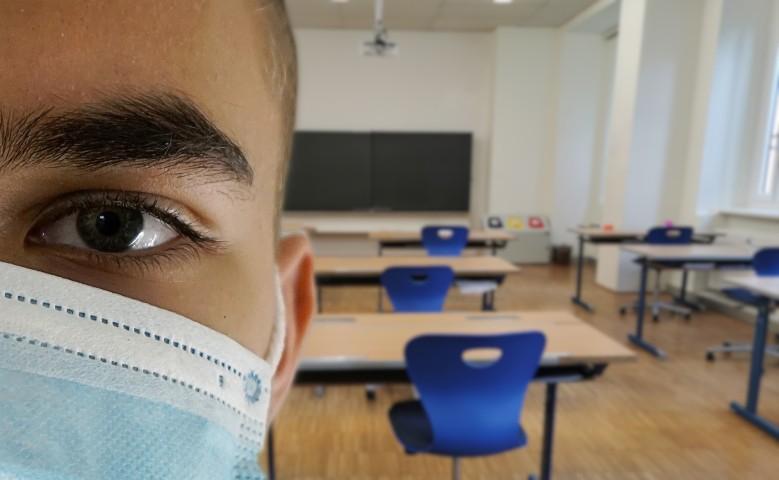 Mann mit medizinischer Maske in Klassenzimmer